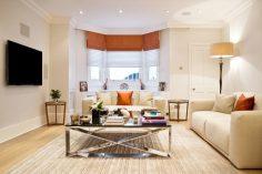 Světlá ložnice s oranžovými doplňky
