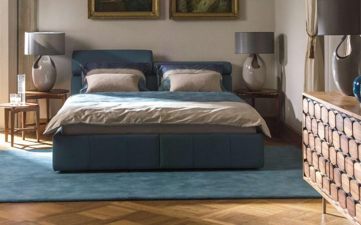Manželská postel spolohovacími polštářky pod hlavu